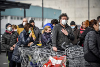 People wearing sanitary masks queue outside a supermarket in Casalpusterlengo, Northern Italy, on Feb. 23, 2020. (Claudio Furlan/Lapresse via AP)