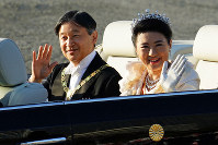In this Nov. 10, 2019, file photo, Japanese Emperor Naruhito, left, and Empress Masako wave during the royal motorcade in Tokyo. (AP Photo/Eugene Hoshiko)