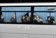 Diamond Princess passengers who had been released from quarantine and were being driven to a chartered plane are seen waving to reporters from a bus in Tsurumi Ward, Yokohama, on Feb. 17, 2020. (Mainichi/Kimi Takeuchi)