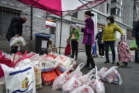 In this Feb. 22 2020, photo, residents wearing protective face masks collect foods distributed by volunteers outside their home in Wuhan in central China's Hubei province. (Chinatopix via AP)