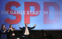 Social Democratic Party, SPD, top candidate and First Mayor of Hamburg Peter Tschentscher, right, celebrates with supporters after exit polls for the Hamburg state elections announced in Hamburg, Germany, on Feb. 23, 2020. (Christian Charisius/dpa via AP)