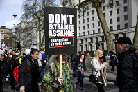 Demonstrators march to protest against the extradition of Wikileaks founder Julian Assange, in London, on Feb. 22, 2020. (AP Photo/Alberto Pezzali)