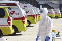 Ambulances gather as a member of paramedic wearing protective gears walk in Daegu, South Korea, on Feb. 23, 2020. (Kim Hyun-tai/Yonhap via AP)
