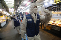 Workers wearing protective gears arrive to spray disinfectant as a precaution against the coronavirus at a market in Seoul, South Korea, on Feb. 24, 2020. (AP Photo/Ahn Young-joon)
