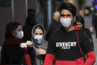 Pedestrians wearing protective masks walk in downtown Tehran, Iran, on Feb. 23, 2020. (AP Photo/Ebrahim Noroozi)