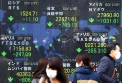 マスクをした人たちが映り込む、新型コロナウイルスの影響で世界的に下落した株価を示す電光掲示板=東京・八重洲で2020年2月25日午前、小川昌宏撮影