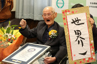 Chitetsu Watanabe, confirmed by Guinness World Records as the oldest living man, holds a certificate next to a work of calligraphy which reads