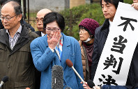 Toshiko Naito, center, one of the plaintiffs, wipes a tear in Tokyo's Chiyoda Ward on Feb. 25, 2020, after the Supreme Court dismissed her and two other plaintiffs' demands that they be recognized as suffering from atomic bomb-related diseases. (Mainichi/Takehiko Onishi)