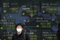 A man stands in front of an electronic stock board showing Japan's Nikkei 225 index and other city's index at a securities firm in Tokyo, on Feb. 25, 2020. (AP Photo/Eugene Hoshiko)