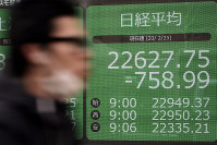 A man walks past an electronic stock board showing Japan's Nikkei 225 index at a securities firm in Tokyo, on Feb. 25, 2020. (AP Photo/Eugene Hoshiko)