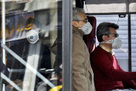 A public bus driver, right, and commuters wear masks to help guard against the coronavirus in downtown Tehran, Iran, on Feb. 23, 2020. (AP Photo/Ebrahim Noroozi)