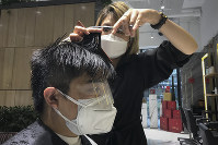A barber wearing a protective face mask cuts a client's hair with an eye cover and face mask at a hair salon in Beijing, on Feb. 24, 2020. (AP Photo/Olivia Zhang)