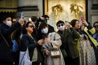 People, some wearing sanitary masks, take photos in central Milan, Italy, on Feb. 24, 2020. (Claudio Furlan/Lapresse via AP)