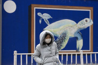A resident wearing mask walks near a mural outside a school that's closed in Beijing, China, on Feb. 25, 2020. (AP Photo/Ng Han Guan)