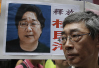In this June 18, 2016 file photo, a picture of missing bookseller Gui Minhai is shown on a placard beside freed Hong Kong bookseller Lam Wing-kee, as the protesters are marching to the Chinese central government's liaison office in Hong Kong. (AP Photo/Kin Cheung)