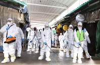 Workers wearing protective suits spray disinfectant as a precaution against the coronavirus at a market in Bupyeong, South Korea, on Feb. 24, 2020. (Lee Jong-chul/Newsis via AP)