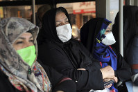 Commuters wear masks to help guard against the Coronavirus on a public bus in downtown Tehran, Iran, on Feb. 23, 2020. (AP Photo/Ebrahim Noroozi)