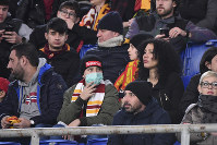 An AS Roma fan wears a sanitary mask as he watches the Italian Serie A soccer match between Roma and Lecce at the Olympic stadium in Rome, on Feb. 23, 2020. (Alfredo Falcone/LaPresse via AP)
