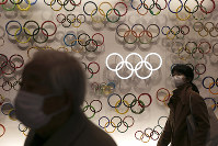 Two people wear masks as they visit the newly opened Japan Olympic Museum located near the New National Stadium on Feb. 23, 2020, in Tokyo. (AP Photo/Jae C. Hong)