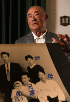 Isao Harimoto is seen speaking about his family, with an image labeling some of its members in the foreground, in Tokyo on Jan. 13, 2020. (Mainichi/Naohiro Yamada)