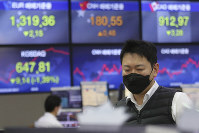 A currency trader watches monitors at the foreign exchange dealing room of the KEB Hana Bank headquarters in Seoul, South Korea, on Feb. 26, 2020. (AP Photo/Ahn Young-joon)