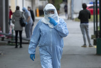 A health worker wears protective suit at the infectious disease clinic in Zagreb, Croatia, where the first coronavirus case in Croatia is hospitalized, on Feb. 25, 2020. (AP Photo/Darko Bandic)
