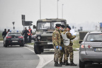 Italian Army soldiers and police check transit to and from the cordoned areas near Turano Lodigiano, Northern Italy, on Feb. 25, 2020. (Claudio Furlan/Lapresse via AP)