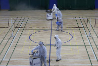 Workers in protective suits spray disinfectant as a precaution against the COVID-19 at an indoor gymnasium in Seoul, South Korea, on Feb. 25, 2020. (AP Photo/Lee Jin-man)
