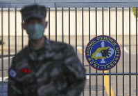 In this Feb. 21, 2020 photo, a South Korean marine wearing a mask stands in front of the Navy Base after a soldier of the unit was confirmed to have been infected with the coronavirus on Jeju Island, South Korea. (Woo Jang-ho/Yonhap via AP)