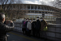 Tourists wear masks as they pause for photos with the New National Stadium, a venue for the opening and closing ceremonies at the Tokyo 2020 Olympics, on Feb. 23, 2020, in Tokyo. (AP Photo/Jae C. Hong)
