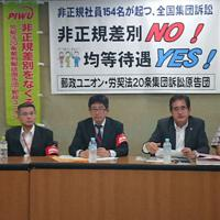 待遇差の改善を求め提訴し、記者会見する代理人の棗一郎弁護士(左から4人目)と郵政ユニオンのメンバーたち=東京都千代田区霞が関の厚労省記者クラブで