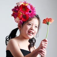 選んだ赤いガーベラを手にカメラマンに笑顔を見せる石井杏奈ちゃん=大阪府八尾市で、梅田麻衣子撮影