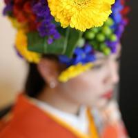 髪や頭に花を装飾し「発芽」させていく=大阪府八尾市で、梅田麻衣子撮影