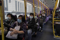 Passengers wears face masks as a precaution against the COVID-19 virus while sitting in a bus in Hong Kong, on Feb. 27, 2020. (AP Photo/Kin Cheung)