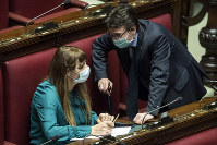 Lawmakers Matteo Dall'Osso, right, and Maria Teresa Baldini wear sanitary mask during a work session in the Italian lower chamber, on Feb. 25, 2020. (Roberto Monaldo/LaPresse via AP)