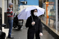 A pedestrian wears a mask and gloves to help guard against the Coronavirus, in downtown Tehran, Iran, on Feb. 25, 2020. (AP Photo/Ebrahim Noroozi)