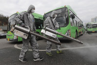 Workers wearing protective suits spray disinfectant as a precaution against the coronavirus at a bus garage in Seoul, South Korea, on Feb. 26, 2020. (AP Photo/Ahn Young-joon)