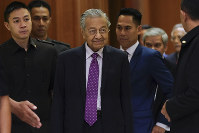Malaysian interim leader Mahathir Mohamad, center, arrives for a press conference at his office in Putrajaya, Malaysia, Thursday, Feb. 27, 2020. (AP Photo/Vincent Thian)