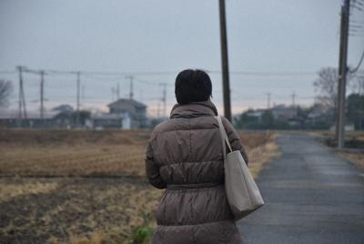 人けのない田畑の間を通り、職場を後にする山本恵さん(仮名)=2020年1月8日、中川聡子撮影