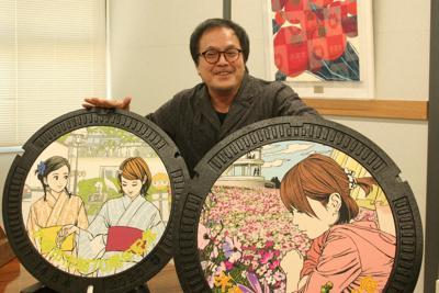 自身が描いたイラストのマンホール蓋を前に笑顔を見せる江口寿史さん=熊本県水俣市で2020年2月27日、山本泰久撮影