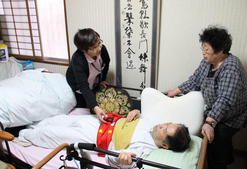 夫を介護する妻(左)とアドバイスをするヘルパー(右)