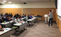 A group of athletes are seen being lectured by an expert on safe use of social media as an Olympian, in this image provided by the Japan Olympic Committee.