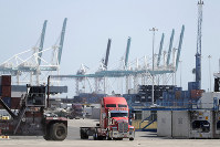 In this Feb. 14, 2020 photo, a truck leaves the docks at PortMiami in Miami. On Feb. 27. (AP Photo/Wilfredo Lee)