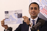 Italian Foreign Minister Luigi di Maio holds up a map of Italy showing the municipalities in regions of Lombardy and Veneto where it is not possible to travel, during a press conference at the foreign press association, in Rome, on Feb. 27, 2020. (AP Photo/Alessandra Tarantino)