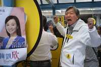 In this Nov. 25, 2018 file photo, pro-democracy candidate Lee Cheuk-yan shouts slogans next to an election poster of establishment candidate Chan Hoi-yan during a by-election campaign at the voting day in Hong Kong. (AP Photo/Vincent Yu)