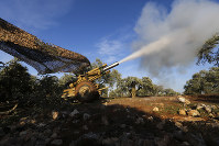 Turkish backed rebel fighters fire a howitzer toward Syrian government positions near the village of Neirab in Idlib province, Syria, on Feb. 20, 2020. (AP Photo/Ghaith Alsayed)