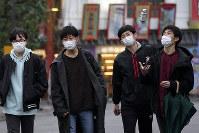 Pedestrians wear masks, on Feb. 26, 2020, in Tokyo. (AP Photo/Eugene Hoshiko)