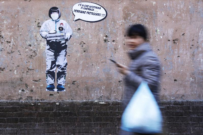 マスク姿の女性が「無知の感染が拡大しています。身を守らなければならない!」と呼びかける皮肉が描かれた壁=ローマで2月6日、AP