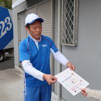 赤ちゃんへの手紙執筆を勧めるチラシを手渡すアート引越センターの社員(左)=大阪府で2020年2月25日、西村浩一撮影