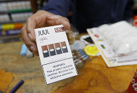 In this June 17, 2019, file photo, a cashier displays a packet of tobacco-flavored Juul pods at a store in San Francisco. (AP Photo/Samantha Maldonado)